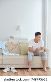 Smiling Asian young man sitting on couch with smartphone in his hands
