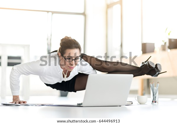 Smiling assistant doing yoga in office. She tired of sitting. Flexibility concept