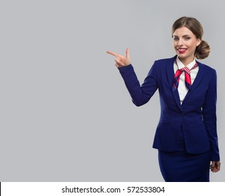 Smiling assistant pointing to the left with finger and demonstrating it.