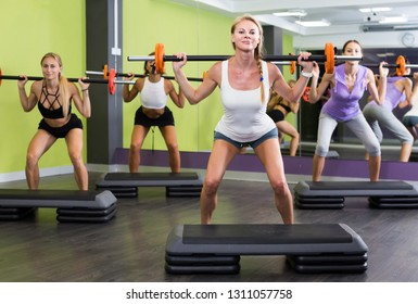 Smiling athletic girls during workout in gym with barbell