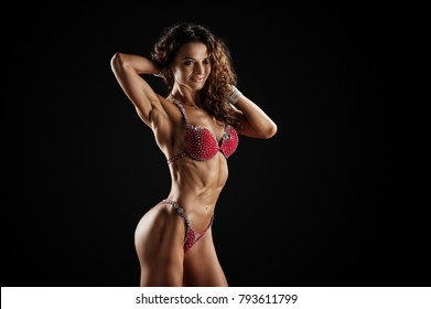 Smiling athletic woman in red bikini showing muscles on dark background. Copy space