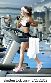Smiling athletic woman running on a treadmill