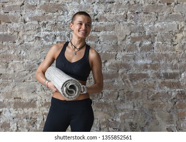 smiling athletic woman with yoga exercise mat standing near brick wall, looking at camera