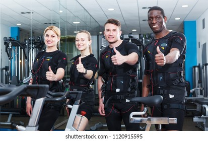 Smiling athletic young people ready for electric muscle stimulation workout in fitness center