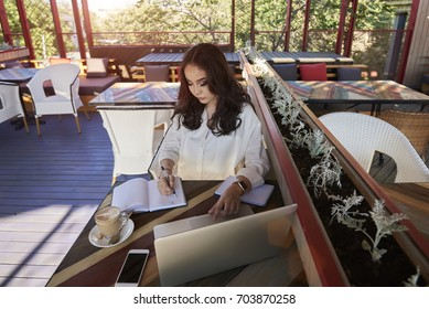 Smiling attractive asian designer making sketch in notebook satisfied with creating solution for project while sitting in coffee shop interior
