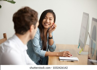 Smiling attractive asian woman talking to male colleague at work sharing office desk with desktops, friendly multiracial coworkers interns having pleasant fun conversation at workplace together