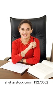 Smiling, attractive brunette businesswoman at her desk, dressed in bright red, isolated against white.