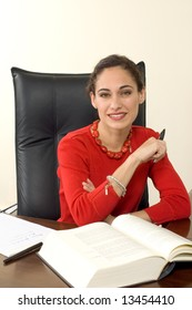 Smiling, attractive brunette businesswoman at her desk, dressed in bright red, shot against white.