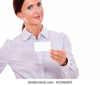 Smiling attractive, brunette businesswoman, looking at the camera with her long hair tied back, wearing a button down shirt, holding a blank visit card with one hand with a white background