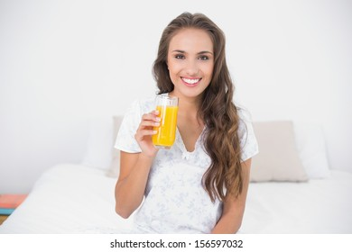Smiling attractive brunette holding a glass of orange juice in bright bedroom
