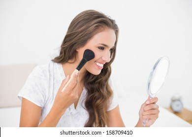 Smiling attractive brunette using a brush and a mirror in bright bedroom