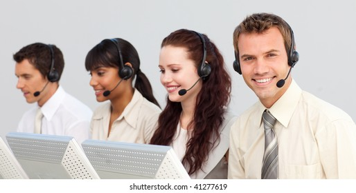 Smiling attractive businessman with a headset on working in a call center