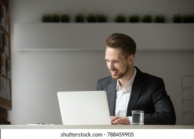 Smiling attractive businessman working online on computer sitting in suit at office desk, young executive manager looking at laptop screen at workplace, happy man using app for business on pc concept