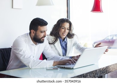 Smiling attractive businesswoman and man having discussion. While drinking coffee at lunch break. Businessman And Businesswoman Meeting In Coffee Shop. Shallow depth of field