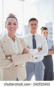 Smiling attractive businesswoman standing with arms folded in front of colleagues