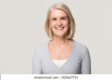 Smiling attractive casual middle aged mature beautiful woman looking at camera, happy healthy old senior lady with blond gray hair posing for portrait isolated on white grey blank studio background