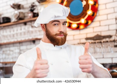 Smiling attractive chef cook showing thumbs up on the kitchen