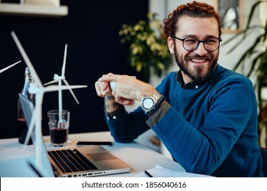 Smiling attractive engineer sitting in his office and drinking coffee on a break. Sustainable development concept.