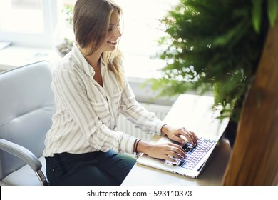 Smiling attractive female freelancer using modern laptop computer and internet connection in coworking office to make distance job editing texts and speeches earning money correcting mistakes online
