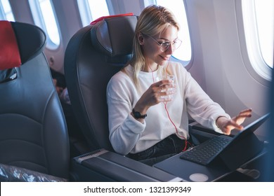 Smiling attractive female passenger watching in earphones online movie on touch pad and during comfortable flight with wireless internet access.Digital nomad.Caucasian young woman using wifi  on board