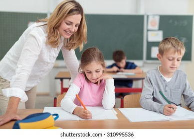 Smiling attractive female teacher checking on a little girls work as she sits alongside a small boy working at a desk in the classroom