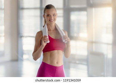 Smiling attractive fitness woman with towel after training
