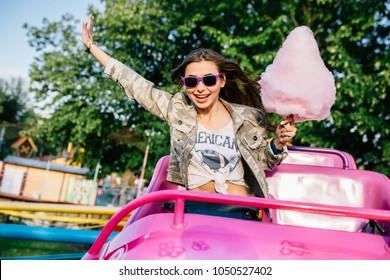 Smiling attractive girl in sunglasses riding a children's roller coaster, enjoying the leisure time, holding a cotton candy. Outdoors.