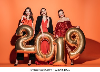 smiling attractive girls in stylish party clothes holding 2019 balloons on orange