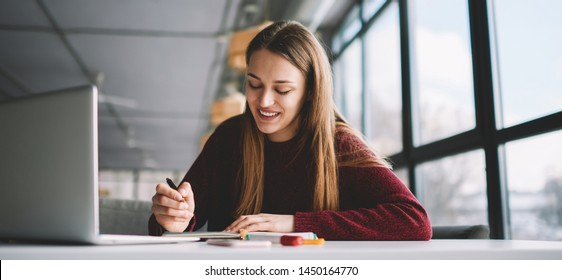Smiling attractive hipster girl doing homework checking information using modern laptop computer, skilled happy female student writing creative ideas to notebook sitting in university campus