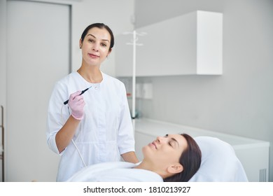 Smiling attractive lady doctor in latex gloves utilizing a needle electrode during the electrosurgical procedure