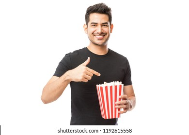 Smiling attractive male pointing at popcorn bucket against white background