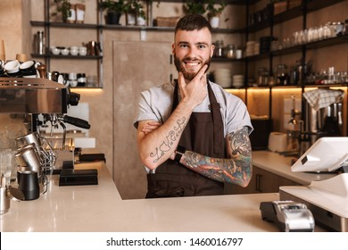 Smiling attractive man barista standing behind the counter at the coffee shop