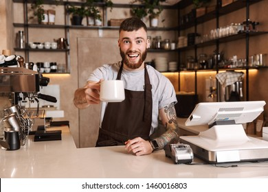 Smiling attractive man barista standing behind the counter at the coffee shop, showing coffee cup