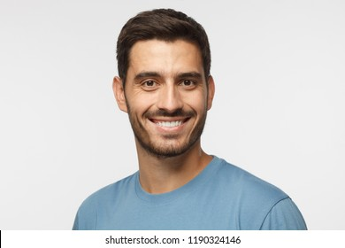 Smiling attractive man in blue t-shirt isolated on gray background