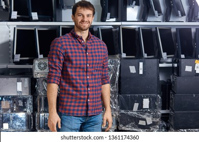 smiling attractive man in checked shirt and jeans posing to the camera in the computer office, close up photo. young man having a rest after repairing a computer