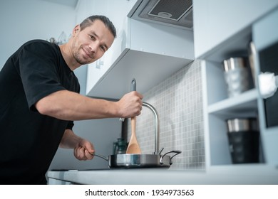 smiling attractive man cooking in pan with wooden spoon at modern home kitchen