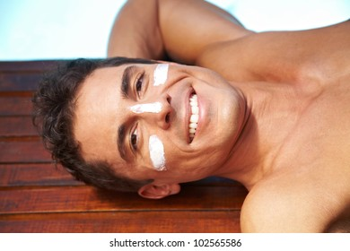 Smiling attractive man with sunscreen on nose and cheeks
