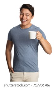 Smiling attractive man wearing a blue shirt and bright pants, holding a mug standing in front of a white background.