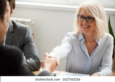 Smiling attractive mature businesswoman handshaking businessman at meeting negotiation, happy hr senior executive woman shaking hand welcoming new hire partner, making deal satisfied with good result