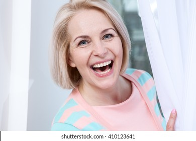 Smiling attractive middle aged woman relaxing at home. The beautiful face close up.