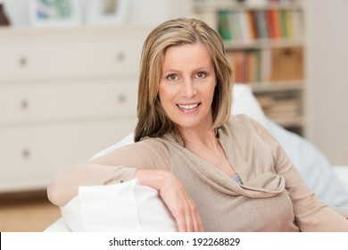 Smiling attractive middle-aged blond woman sitting in a relaxed position with her arm over the back on a sofa in her living room smiling at the camera
