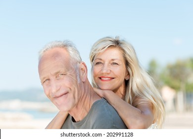 Smiling attractive middle-aged couple relaxing at the beach posing together for a portrait in the hot summer sun