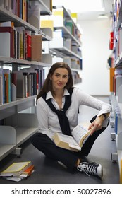Smiling attractive student sitting in between bookshelves in modern university library reading books.