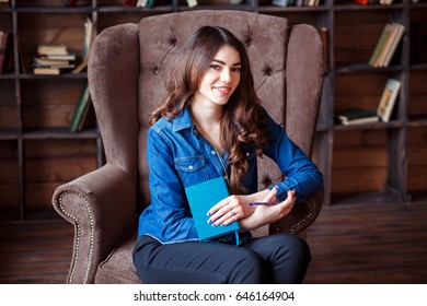 Smiling attractive student woman is holding notebook in her hands. She is in the library sitting in the posh comfortable armchair.