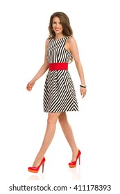 Smiling attractive woman in black and white striped dress and high heels walking and looking at camera, Full length studio shot isolated on white.