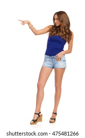 Smiling attractive woman in blue shirt, jeans shorts and cork high heels, pointing and looking away, Full length studio shot isolated on white.
