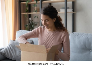 Smiling attractive woman opening big carton box, feeling curious of unpacking internet store order at home. Happy millennial female client satisfied with fast delivery service, online shopping concept