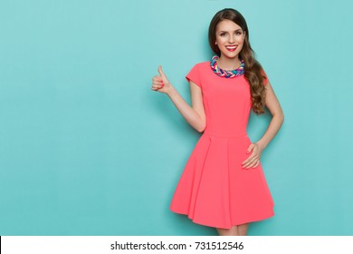 Smiling attractive woman in pink mini dress is posing with hand on hip and showing thumb up. Three quarter length studio shot on turquoise background.