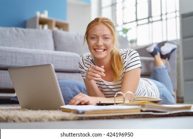 Smiling attractive woman relaxing at home with a laptop computer lying on the floor with her feet in the air studying for university