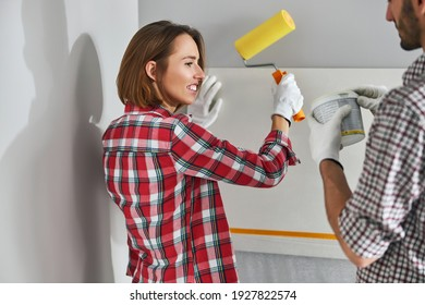 Smiling attractive woman with a roller in her hand and a man with a plastic pail standing by the wall